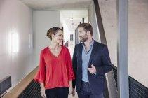 Homme d'affaires et femme d'affaires marchant au bureau — Photo de stock