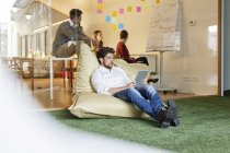Man in office sitting in bean bag — Stock Photo