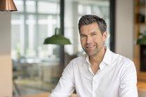Homme d'affaires souriant à la caméra — Photo de stock