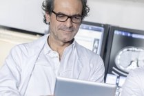Cropped portrait of mature doctor looking at tablet — Stock Photo