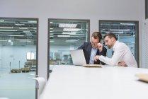 Бизнесмены, использующие ноутбук офис — стоковое фото