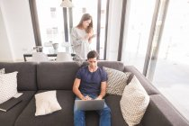 Couple at home using cell phone and laptop — Stock Photo