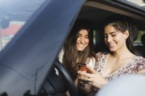 Women using cell phone in car — Stock Photo