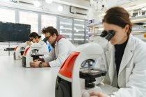 Техников, используя микроскопы в лаборатории — стоковое фото