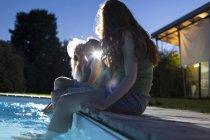 Amigos sentados en la piscina en la noche - foto de stock