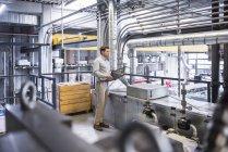 Homme avec documents permanent en usine — Photo de stock