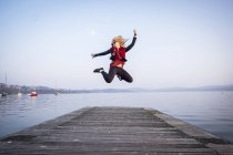 Woman jumping in air on jetty — Stock Photo