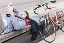 Mann liegt auf Bank mit smartphone — Stockfoto