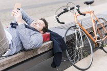 Чоловік лежить на лавці, за допомогою смартфона — стокове фото
