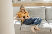 Woman on couch using cell phone — Stock Photo