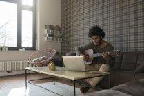 Uomo che suona la chitarra nel salotto — Foto stock