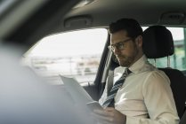 Businessman sitting in car reading files — Stock Photo