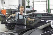 Car mechanic changing car window — Stock Photo