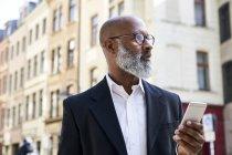 Uomo d'affari tramite smartphone — Foto stock