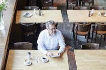 Geschäftsmann sitzt im Café und nutzt Tablet — Stockfoto