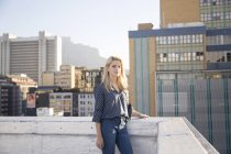 Serious blonde woman standing on rooftop — Stock Photo