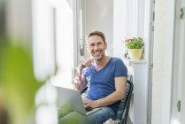 Hombre sentado en el balcón con ordenador portátil - foto de stock