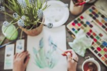 Potted plant and woman painting plants — Stock Photo