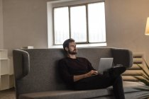 Man sitting with laptop on couch — Stock Photo