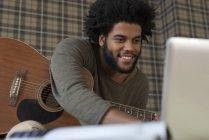 Uomo che suona la chitarra in salotto — Foto stock