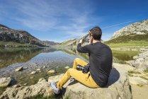 Человек, сидящий на озера Ковадонга — стоковое фото