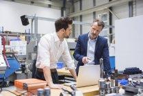 Men using laptop in factory — Stock Photo