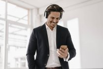 Businessman with cell phone and headphones — Stock Photo