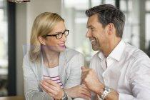 Homme d'affaires et femme avec appareil portatif — Photo de stock