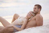 Пара сидящих на пляже — стоковое фото