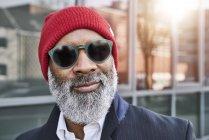 Homem de negócios usando óculos escuros e boné vermelho — Fotografia de Stock