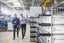 Men walking and talking in factory — Stock Photo