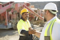 Two quarry workers shaking hands — Stock Photo
