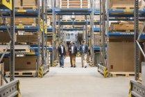 Homens caminhando no armazém da fábrica — Fotografia de Stock