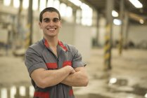 Smiling worker standing in factory — Stock Photo