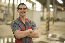 Travailleur souriant debout dans l'usine — Photo de stock