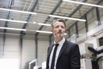 Businessman standing in factory shop floor — Stock Photo