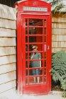 Niño en la caja del teléfono rojo - foto de stock