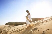 Mãe correndo com a filha na praia — Fotografia de Stock