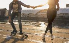 Couple skateboarding at riverside — Stock Photo