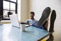 Homem sentado com os pés na mesa — Fotografia de Stock