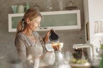 Frau, die Kaffeezubereitung — Stockfoto