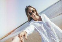 Femme avec des lunettes de soleil tenant la main sur la plage — Photo de stock