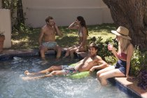 Friends relaxing at swimming pool — Stock Photo