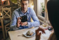 Man taking instant photos of girlfriend — Stock Photo