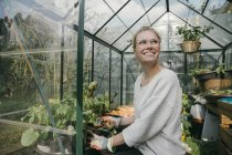 Happy young woman in greenhouse — Stock Photo