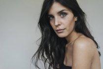 Dark-haired woman looking at camera — Stock Photo