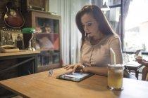 Жінка за допомогою планшетного ПК у кафе — стокове фото
