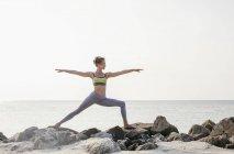 Woman practicing yoga on beach — Stock Photo