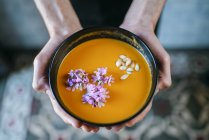 Male hands holding creamed pumpkin soup — Stock Photo