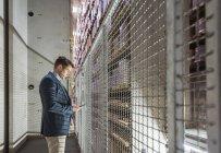 Людина в склад автоматизованого високі стійки, дивлячись на мобільний телефон — стокове фото